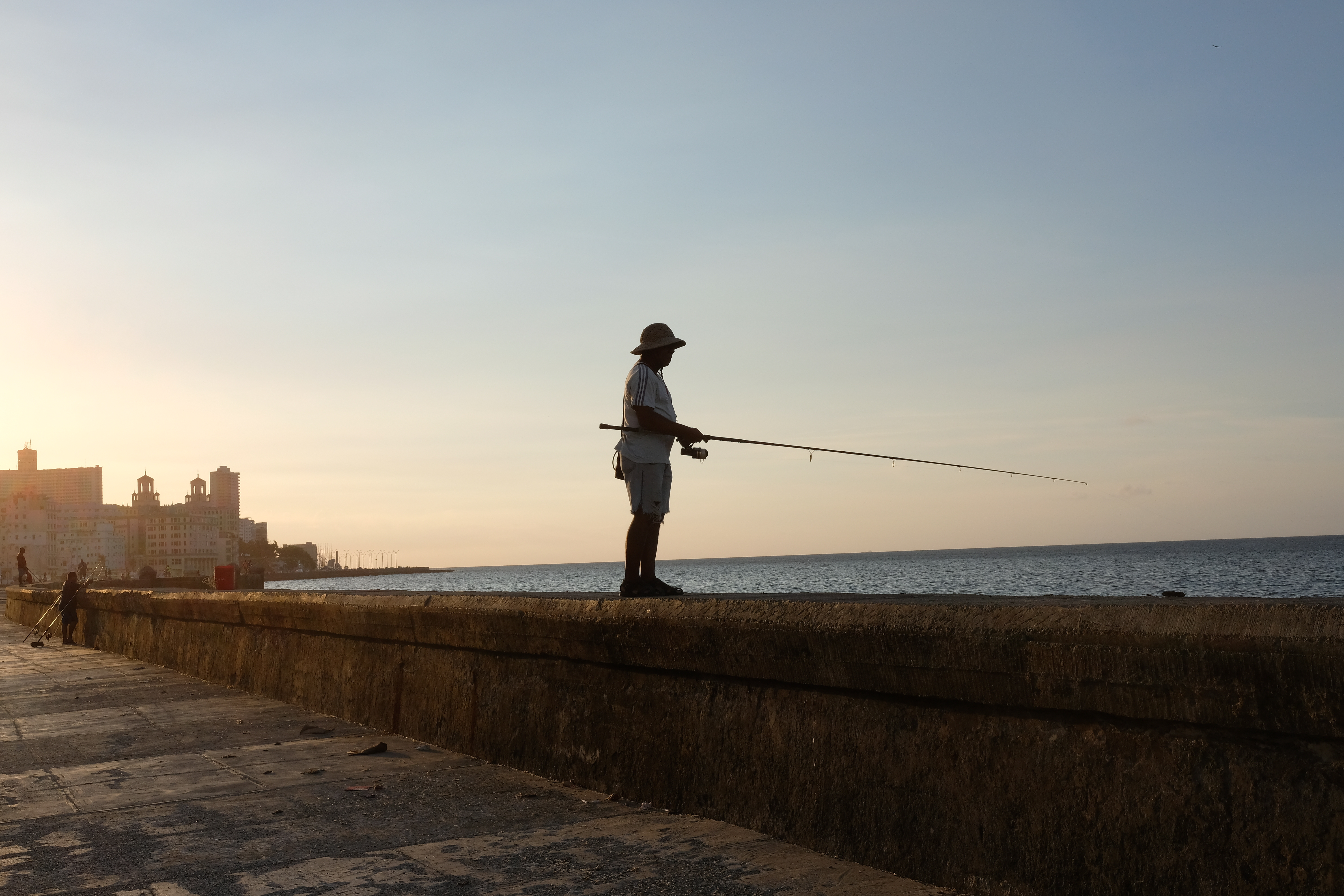 A man fishes from the wall of the Malacon, Havana